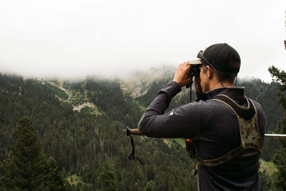 Matthew Weaver looking at landscape through binoculars on a hunting trip