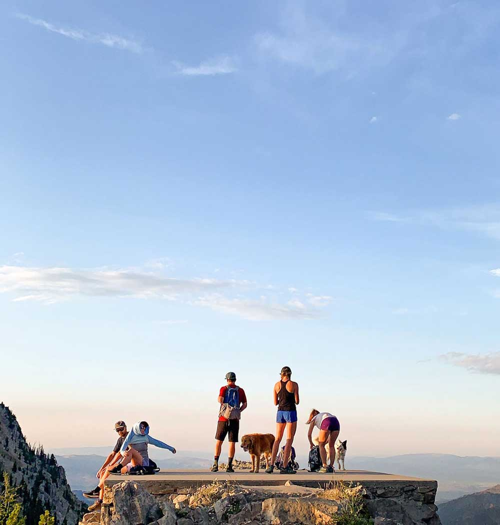 Group of hikers sitting and standing on a mountain plateau