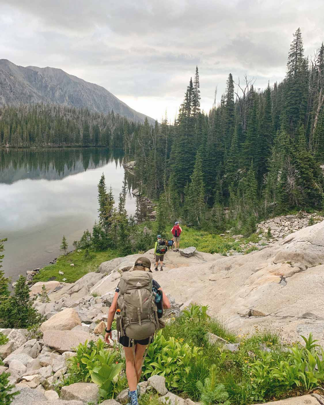 Group backpacking into an alpine lake