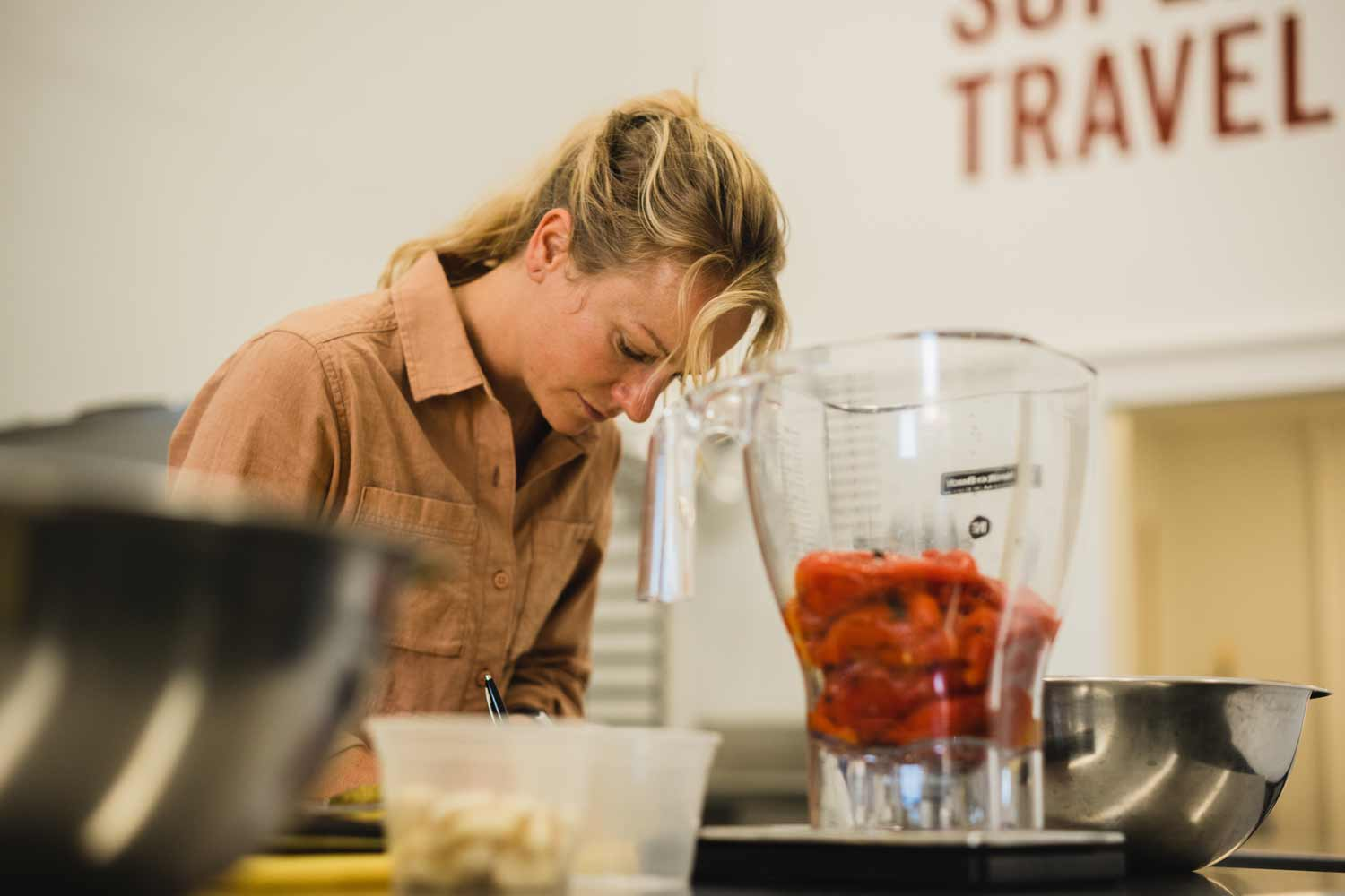 Shannon in kitchen doing product testing, blending roasted red peppers