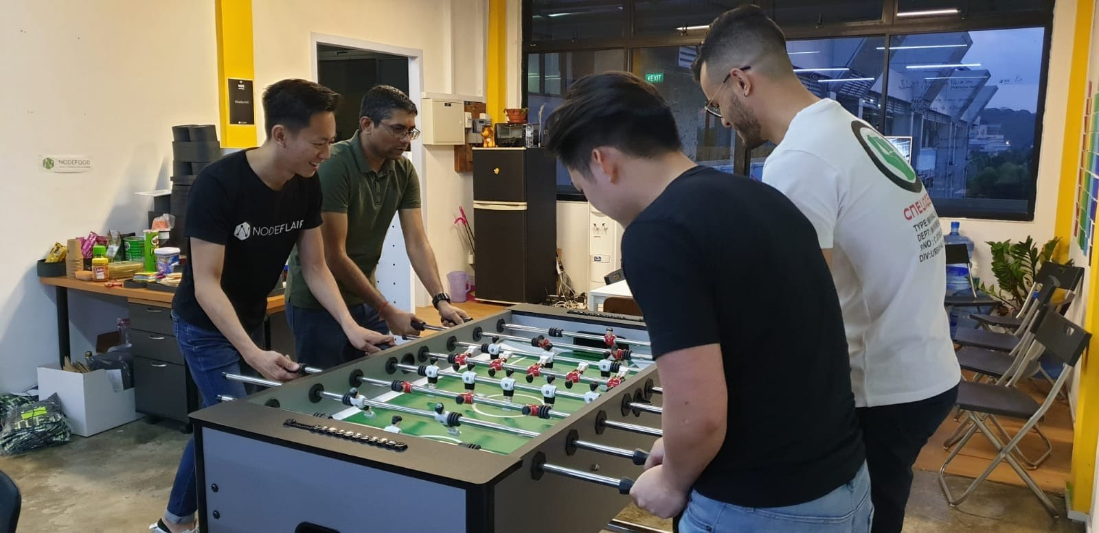 Developers and talent advocates enjoy a game of foosball at the NodeFlair office