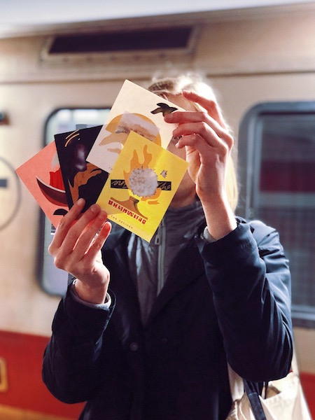 A woman holds four collage cards in front of her face, in front of the T train