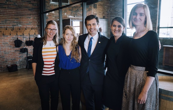 A group of four women stand with presidential candidate Pete Buttigieg