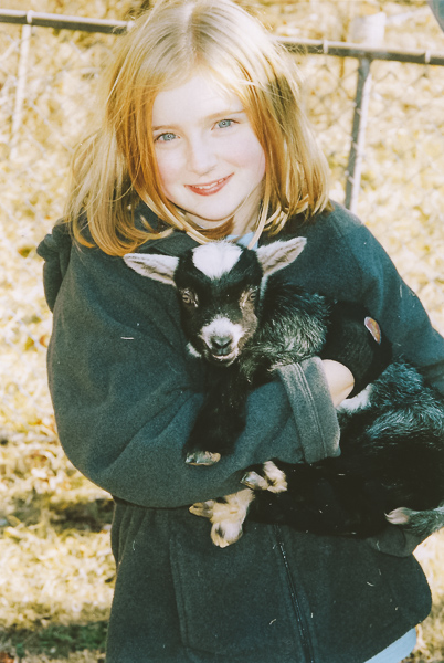 A young girl smiling at the camera holds a baby goat outside