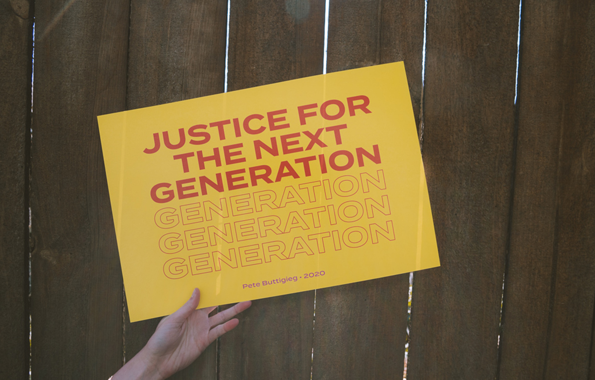 "A sign that says, ""justice for the next generation"" is held up in front of a wooden slat fence"