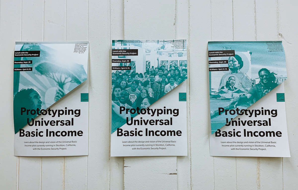 "Three posters are taped to a white wooden slat door. The posters say, ""Prototyping universal basic income"""