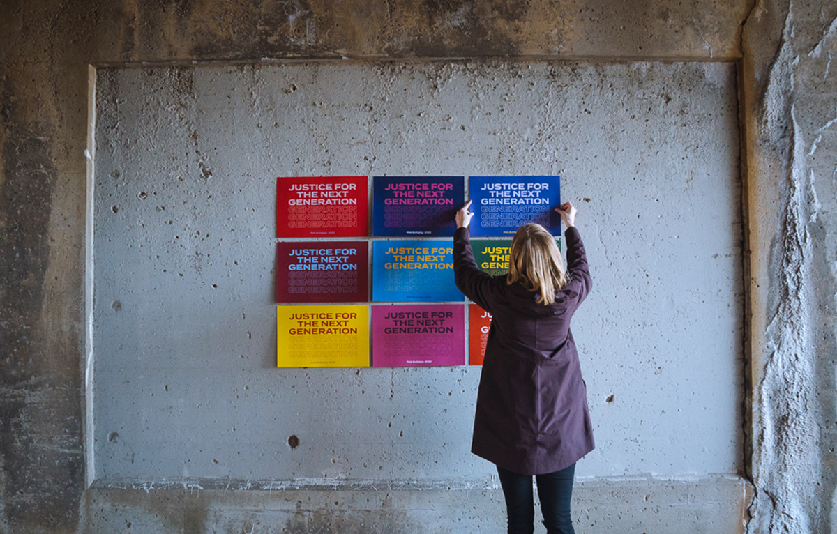 "A woman tapes of a series of nine signs to a cement wall, in different color combinations. The posters all read ""justice for the next generation."""