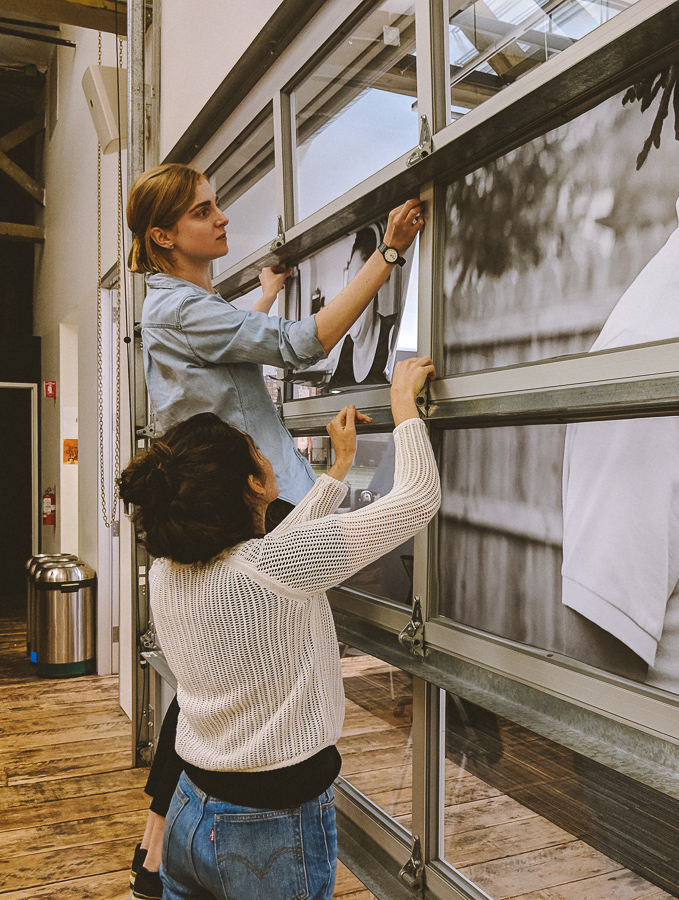 Two women hang translucent portraits of people across a large indoor garage door with glass windows