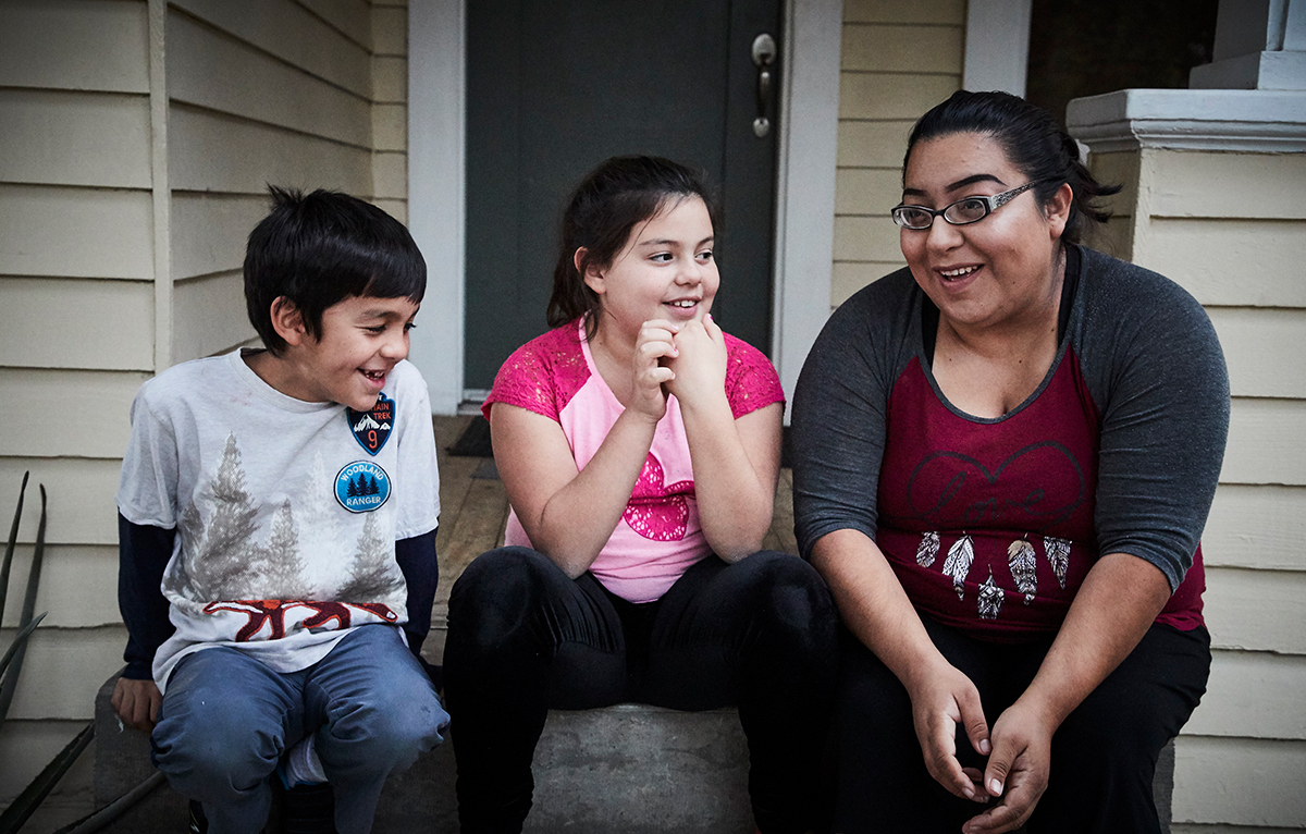 A woman and her two children sit on their front porch steps, laughing and smiling. The woman is telling a story.