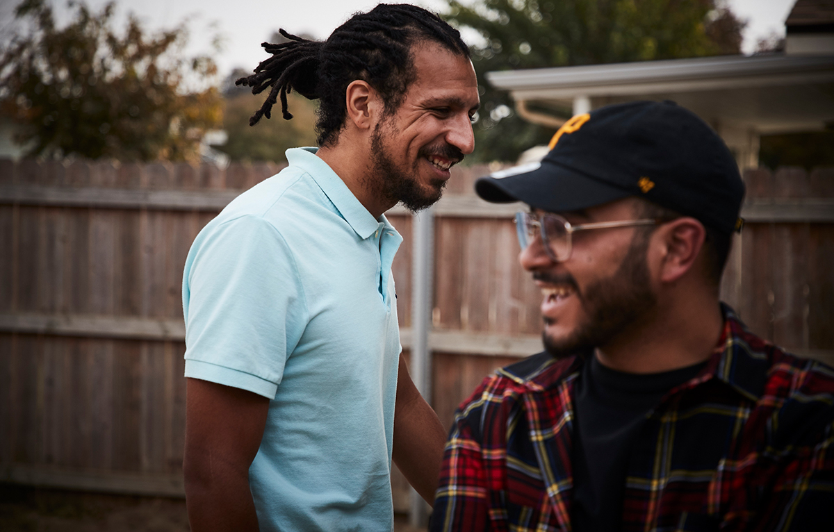 Two men smiling in a fenced in backyard.