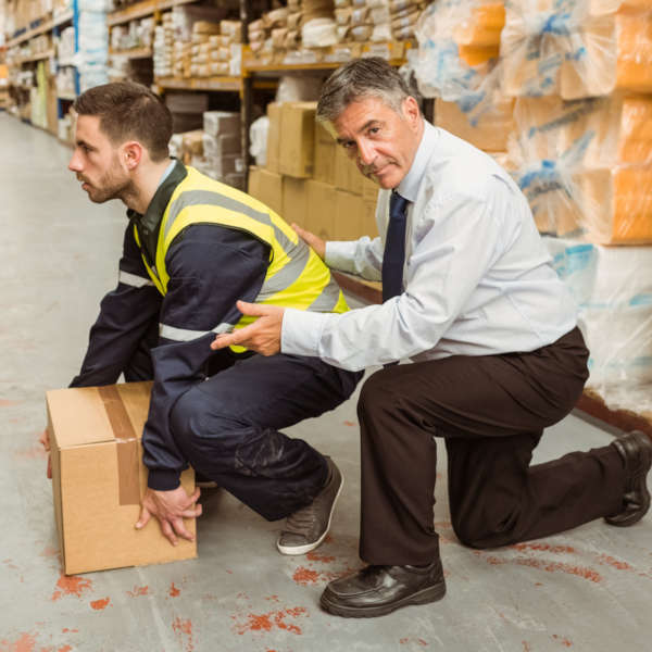 man in suit next to warehouse worker