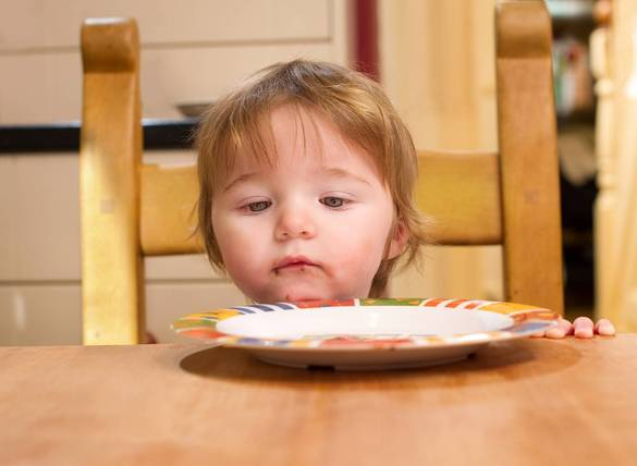 a beautiful little girl stares at her empty plate