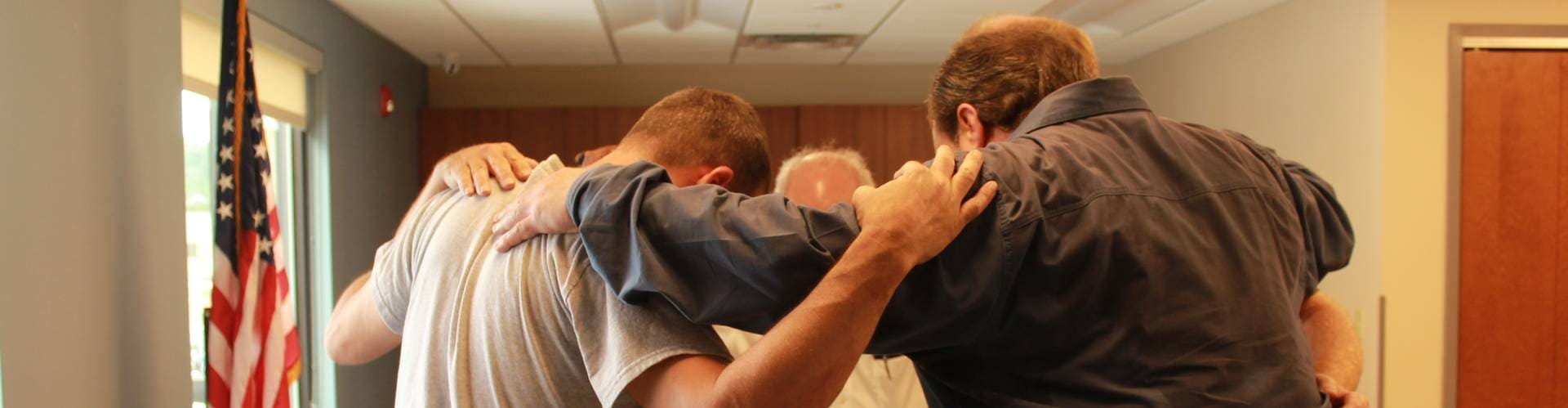 Group prayer session - 5 men lead by counselor