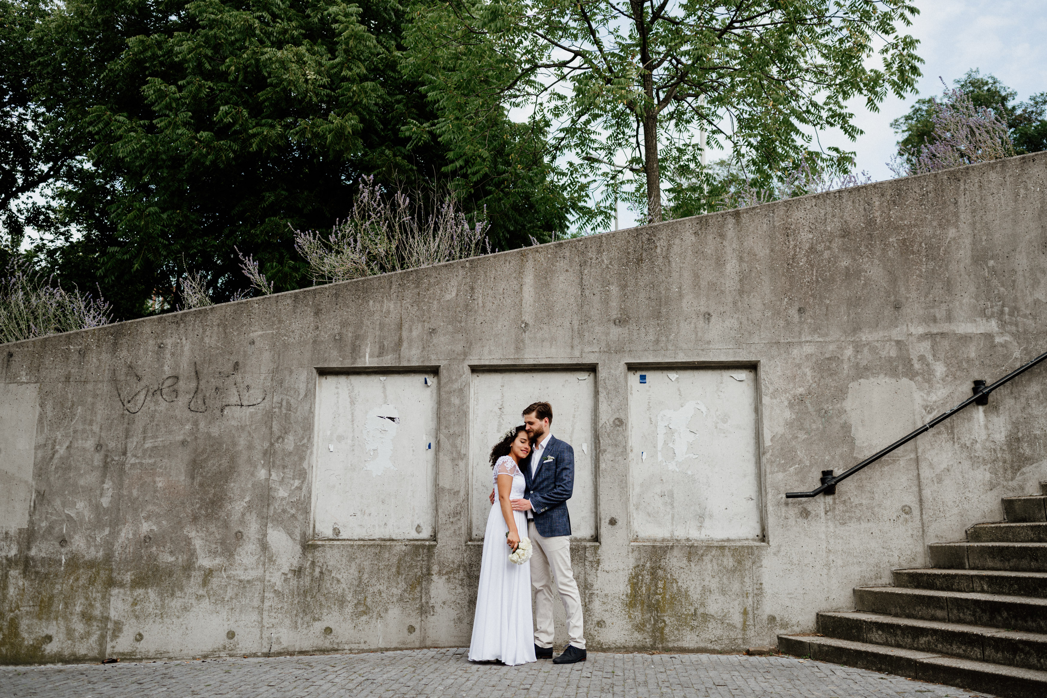 wedding couple in front of concrete wall