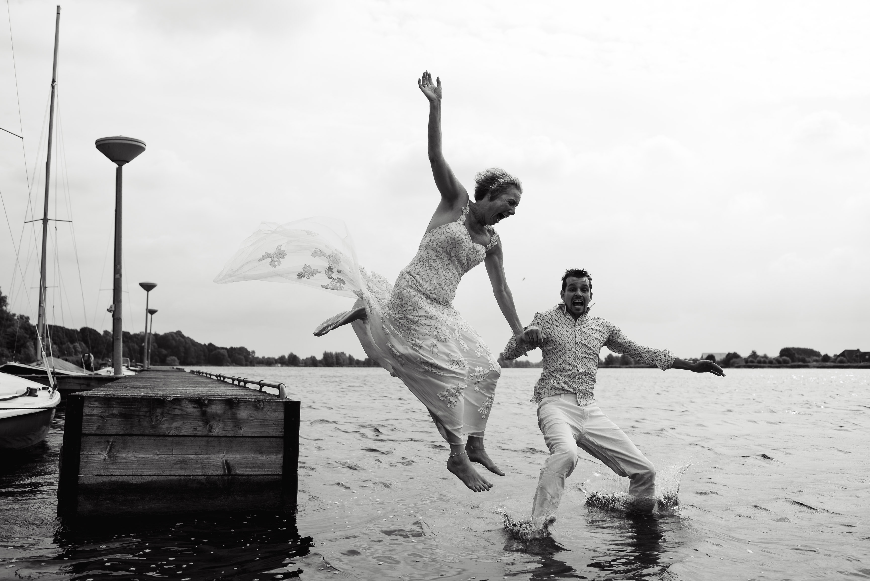 wedding couple jumping in the water