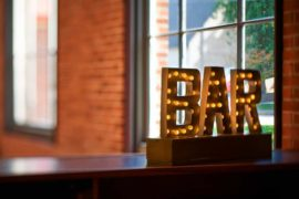 a light up sign that says BAR on a bartop