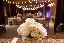 A white flower arrangement on a tabletop at a party