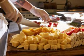 A chef prepares blocks of cheese with strawberries