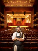 a chef poses in the orchestra seating of the taper auditorium in benaroya hall