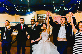 a young bride and groom cheer with their friends