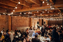 Guests are seated and dining together in a industrial event venue