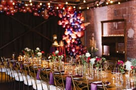 A wedding's dinner reception is set and decorated with a large garland of balloons