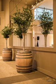 wine barrels with floral arrangements line a mirrored wall