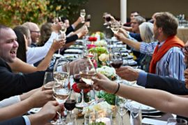 A long table full with guests raise wine glasses for a toast
