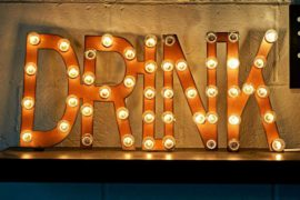 A light up sign that says DRINK