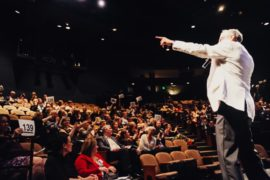 An auctioneer takes the stage at a live auction in an auditorium