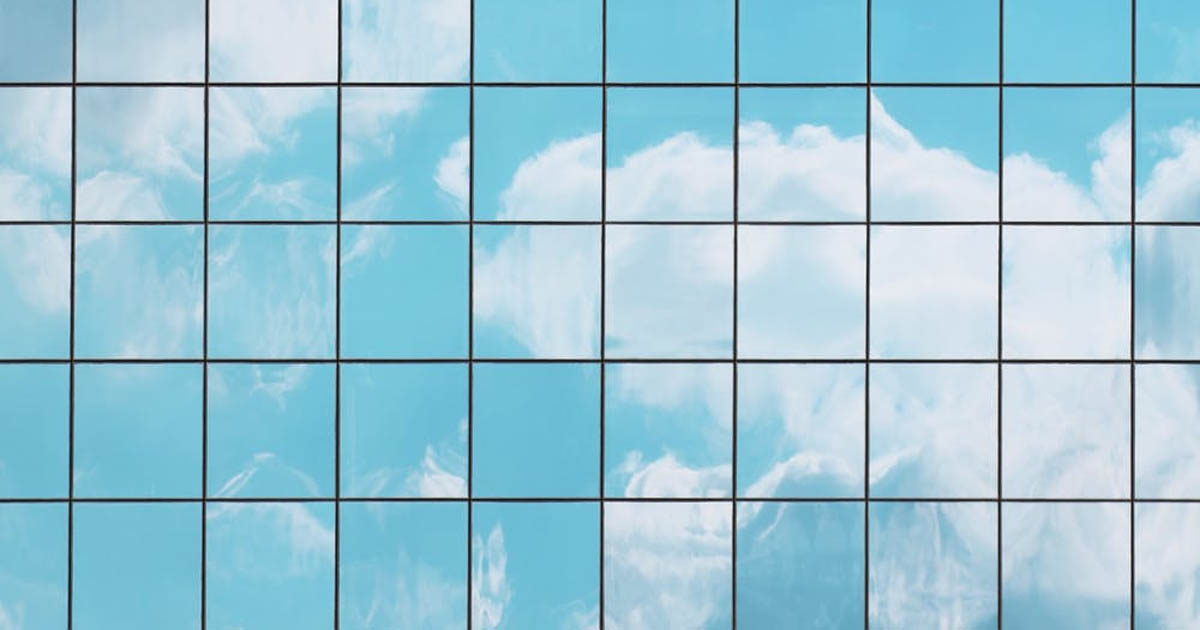 perfectly square windows on a skyscraper reflecting clouds