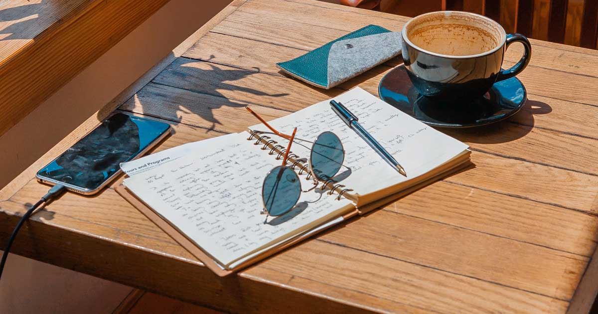 journal on a table with glasses and coffee