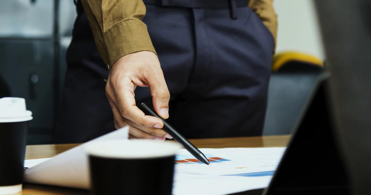 person pointing at paper with a pen