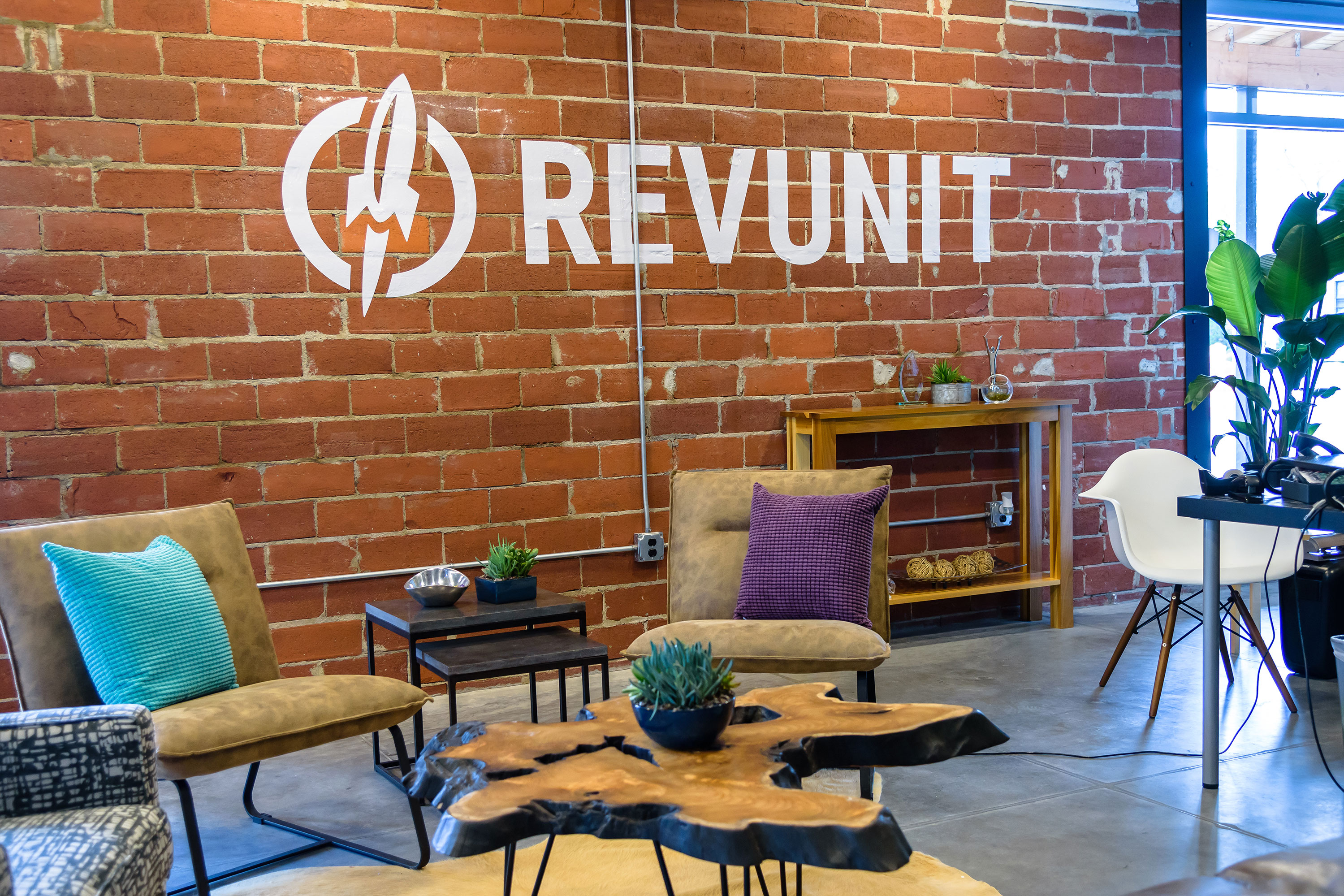 office with brick wall and RevUnit logo