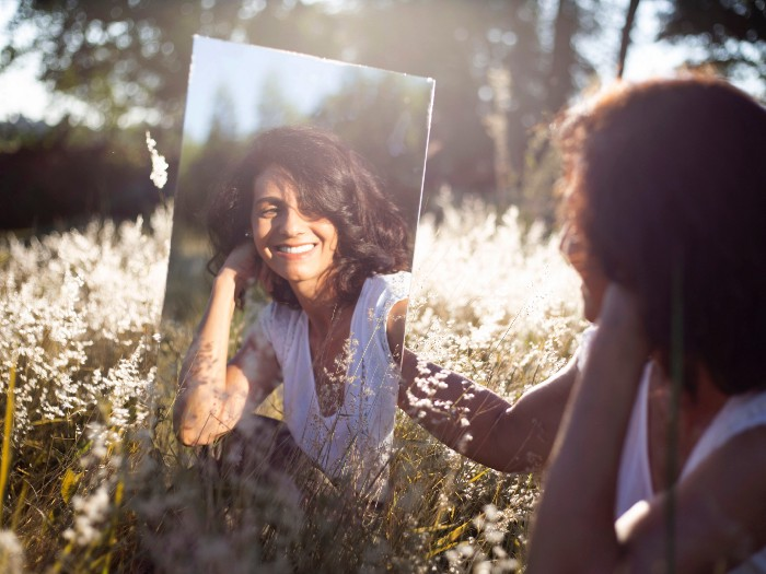 Woman sitting in a grassy meadow holding up a mirror and smiling at her reflection
