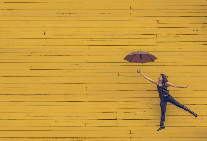 Woman holding an umbrella jumping in front of a mustard yellow wall