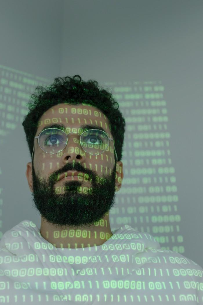 Man staring at a display of binary code
