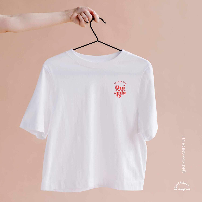 Hand hält weißes T-Shirt mit Logodesign QuiLala Beauty Bar bedruckt.
