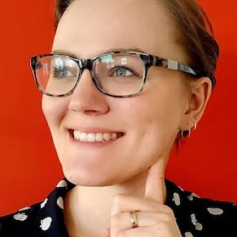 Klientin Sandra Neuditschko Portrait vor rotem Hintergrund.