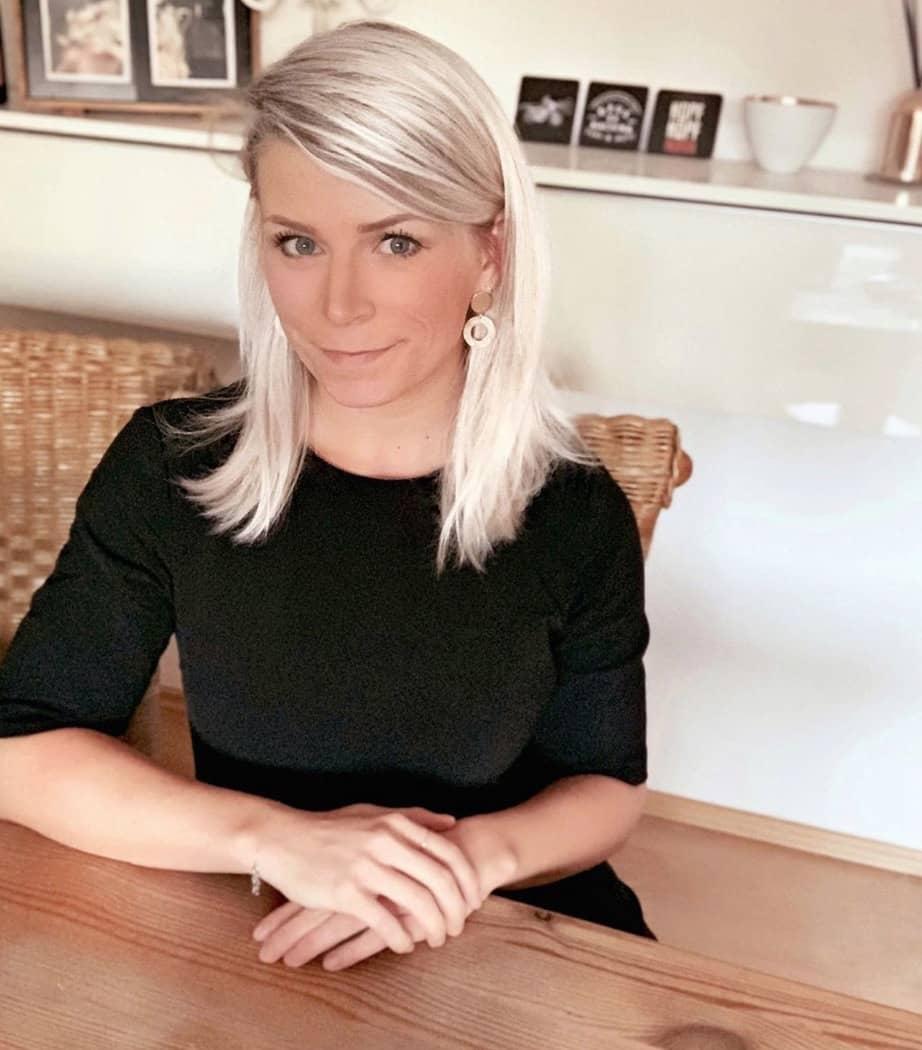 Zuni Sandra Kubera (Markenstrategin für Corporate Design und Branding) sitzt im schwarzen Kleid am Schreibtisch in ihrem Studio.