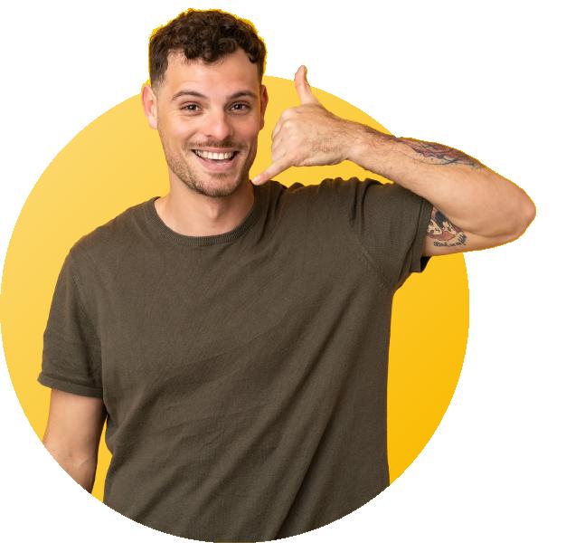 homme souriant faisant un signe d'appeler au téléphone
