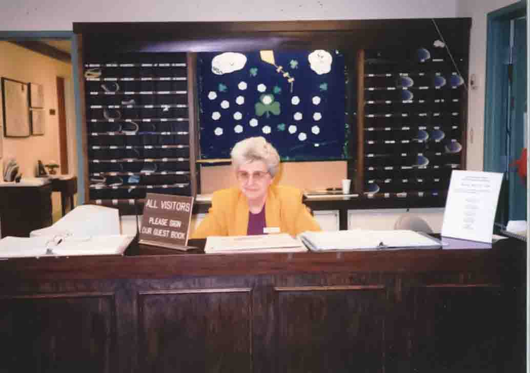 front desk with woman sitting behind desk
