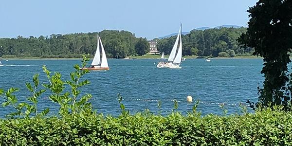 Zwei Segelboote auf dem Chiemsee segeln an Schloss Herrenchiemsee vorbei in der Nähe von  Yager Therapie Hypnose und Coaching Praxis Groenesteyn Muenchen und Prien am Chiemsee