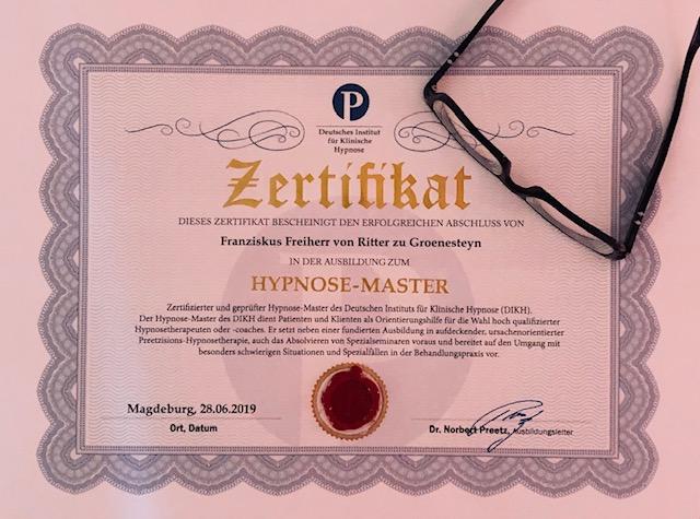 Hypnosemaster Zertifikat auf weißem Papier mit Brille ausgestellt von Dr. Norbert Preetz Magdeburg für  Yager Therapie Hypnose und Coaching Praxis Groenesteyn Muenchen und Prien am Chiemsee