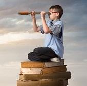 Inneres Kind  auf einem Stapel Bücher entdeckt die Welt Praxis Groenesteyn Hypnotherapie