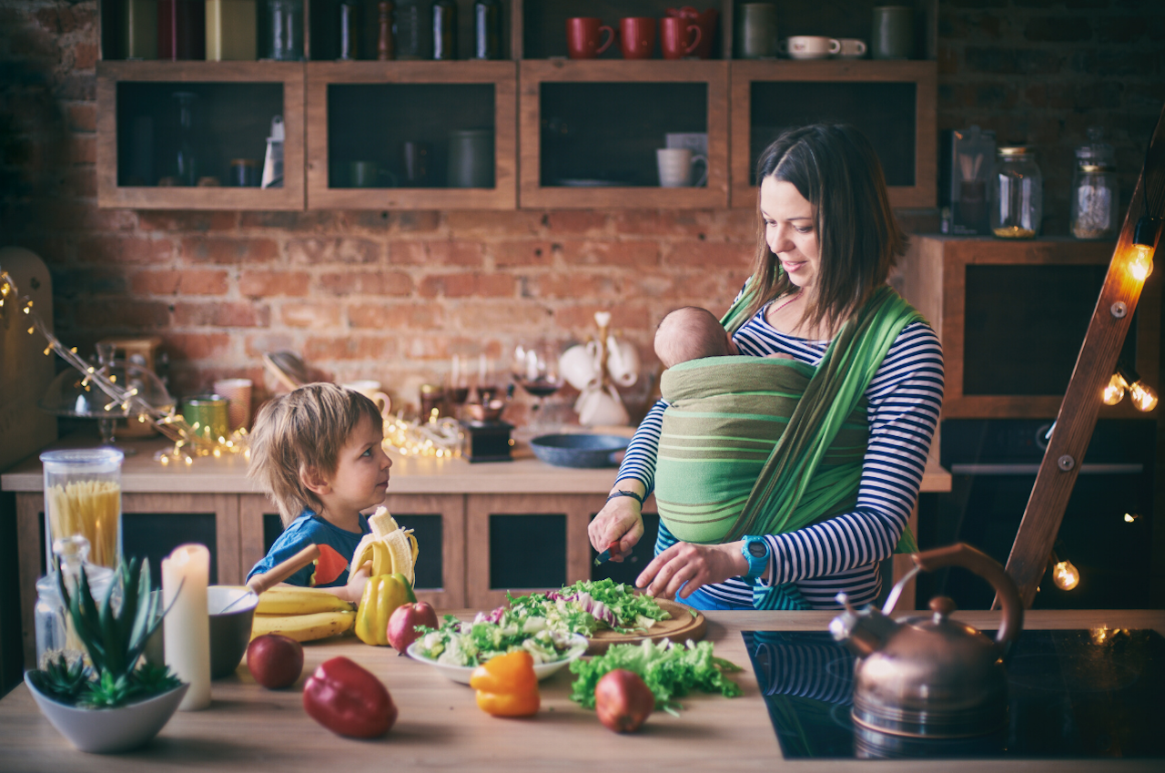 Working mother with a toddler and a baby cooking dinner