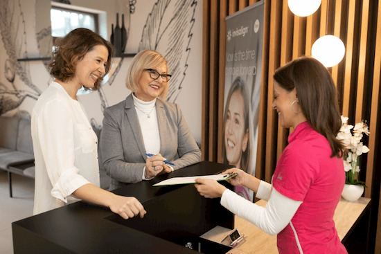 Women smiling and signing up for free dental checkup