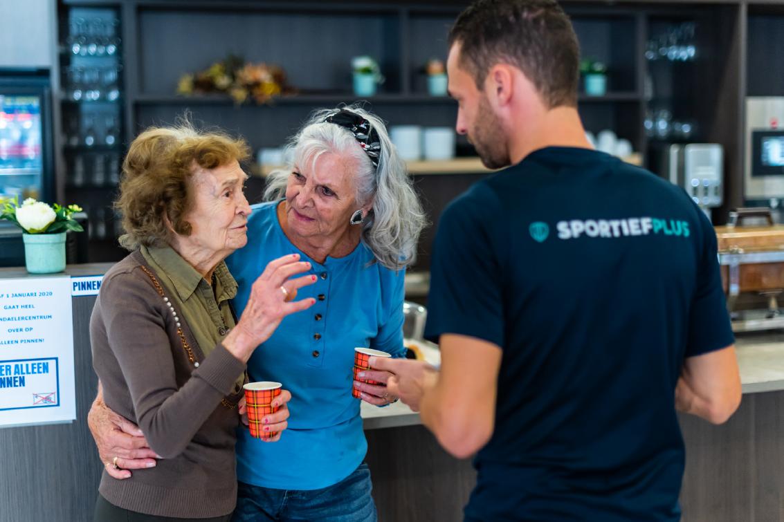 Twee oudere dames worden ondersteund door een sportleraar