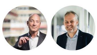 Je ziet twee rond uitgesnede foto's. Links in beeld is Rick Hogenboom, met een witte blouse aan en een zwart colbert. Rechts zien we Bert Moormann, met een blauwgrijze blouse aan en een colbert. Beide foto's hebben een wazige achtergrond en beide mannen lachen.