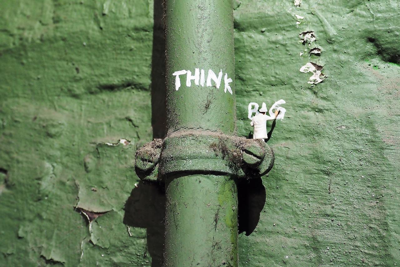 Een groene muur met daarop een waterpijp die ook in diezelfde kleur groen is geschilderd. Op het bevestigingsmateriaal van de waterpijp staat een kleine schilder die aan het schilderen is. Hij schrijft met witte letters 'Think Big' op de muur.